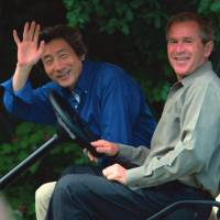 U.S. President George W. Bush poses for a photo alongside Prime Minister Junichiro Koizumi at Camp David near Thurmont, Maryland, in 2001. | KYODO