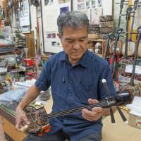 Sanshin maker Toshio Matayoshi plays one of his creations. This instrument originated in China, where it was known as the sanxian. | STEPHEN MANSFIELD