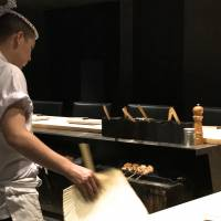 Chef Kohei Onoda waves a sturdy paper fan to keep the charcoal embers at the perfect temperature. | ROBBIE SWINNERTON