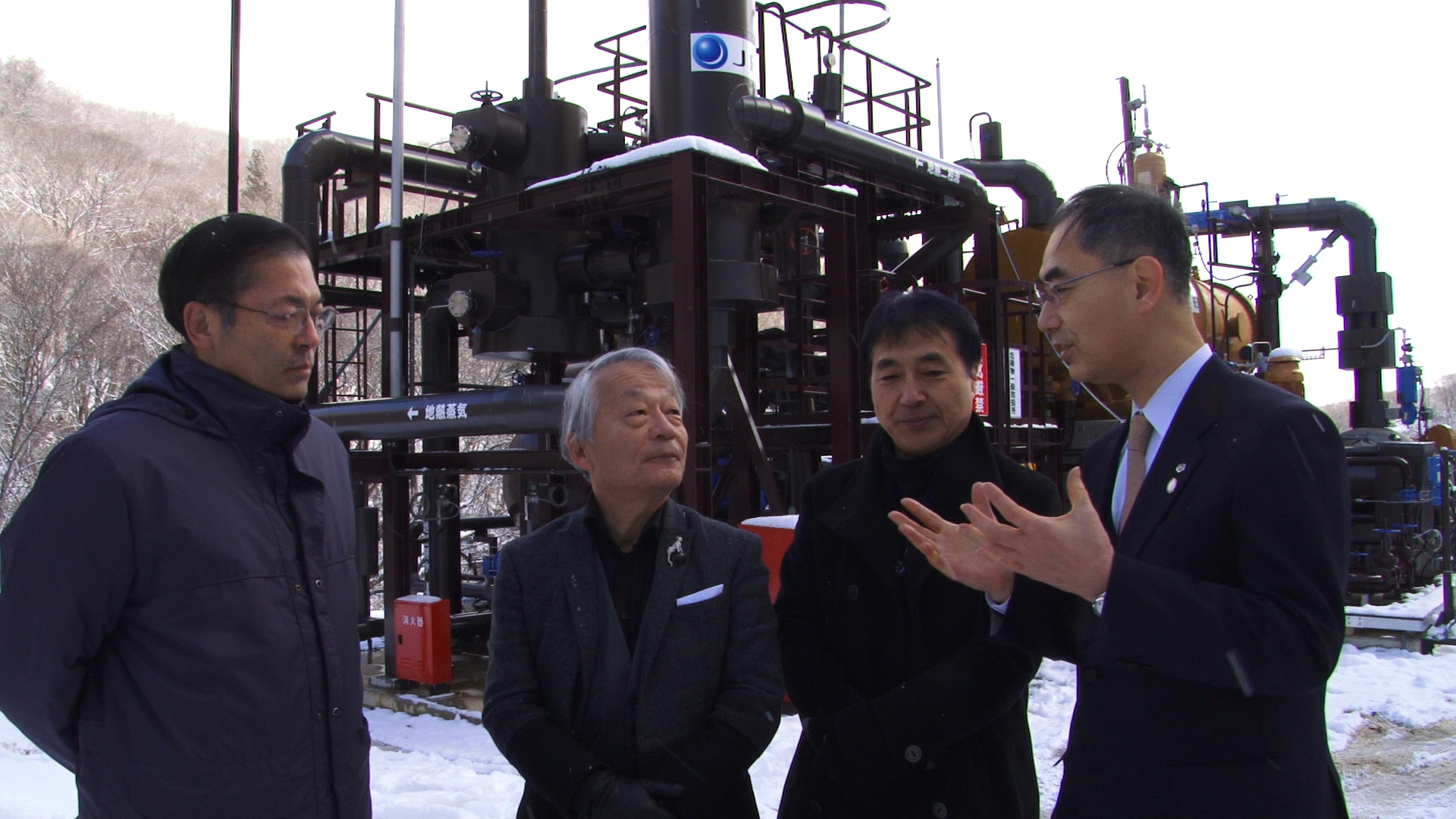 Politics of power: Hiroyuki Kawai (left) and Tetsunari Iida (center) discuss the economics of renewables with a banker in front of a geothermal apparatus in the town of Tsuchiyu Onsen in Fukushima Prefecture.   © K PROJECT