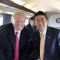 Getting too friendly: U.S President Donald Trump and Prime Minister Shinzo Abe share a moment aboard the presidential helicopter, as seen in a photograph tweeted by Trump in early February. | KYODO