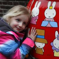 Basically beloved: A girl hugs a Miffy statue outside the Nijntje Museum in Utrecht, Netherlands, on Feb. 17, the day after Dick Bruna, the creator of the white bunny, passed away aged 89. | AP