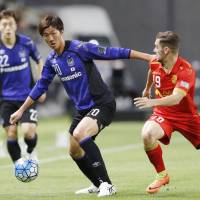 Gamba Osaka's Shun Nagasawa (left) and Adelaide United's Ben Garuccio chase the ball during the first half of Tuesday's Asian Champions League match in Suita, Osaka Prefecture. | KYODO