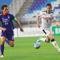 Kawasaki Frontale's Tatsuki Nara (right) and Suwon's Yeom Ki-hun compete for the ball during their Asian Champions League match in Suwon, South Korea, on Tuesday. | AFP-JIJI