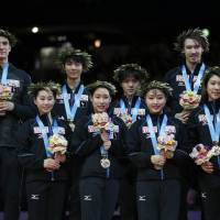 Japan skaters celebrate the team's first-place finish on the podium at the World Team Trophy on Saturday night. | REUTERS