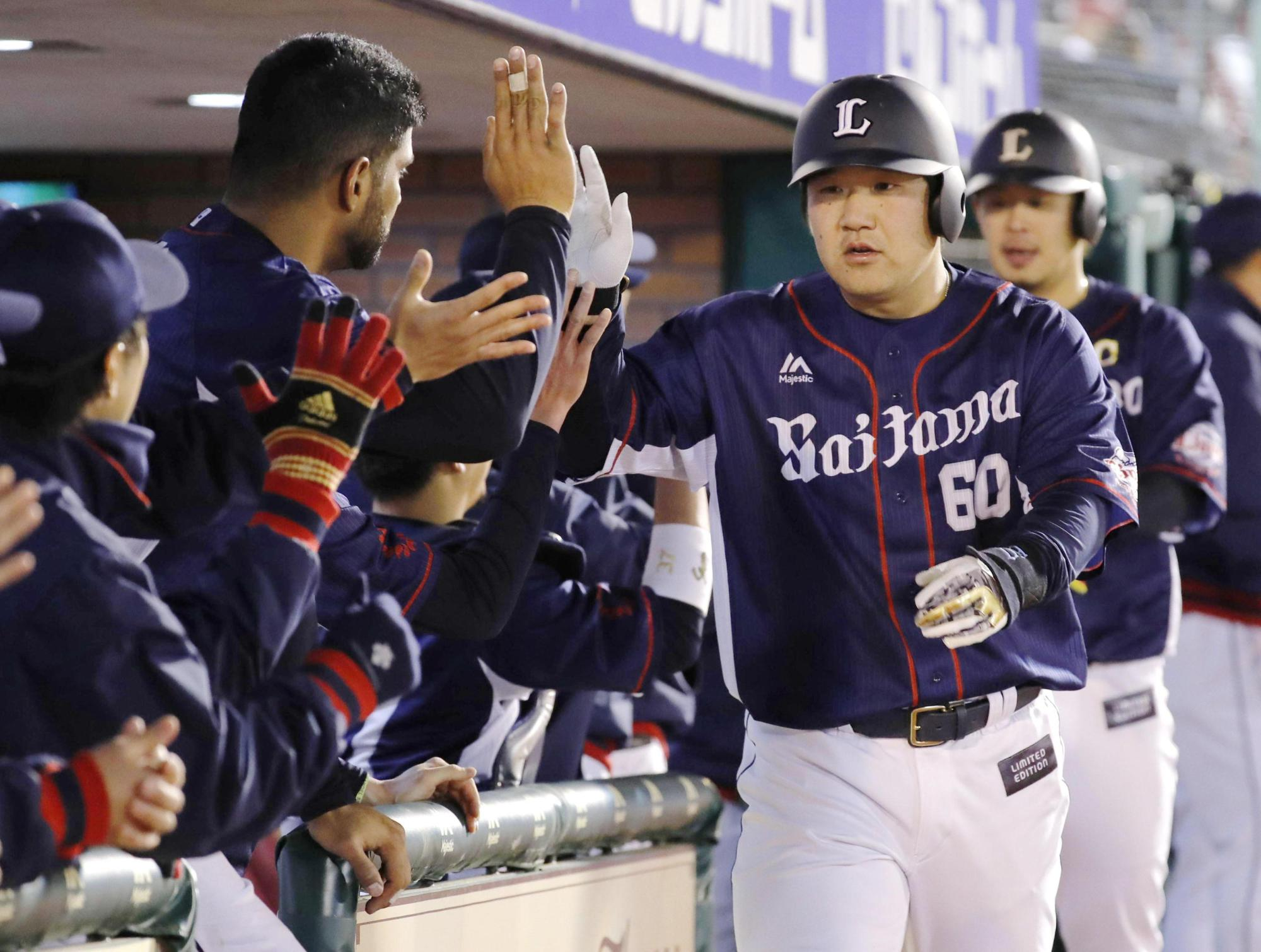 The Lions' Takeya Nakamura is congratulated after hitting a three-run home run during the ninth inning on Wednesday. | KYODO
