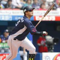 Seibu's Hideto Asamura watches the flight of the ball after hitting an RBI double in the first inning of the Lions' 10-2 win over the Marines on Sunday. | KYODO