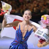 Mao Asada smiles for the crowd at Saitama Super Arena after winning her third world title in March 2014. On Monday, the figure-skating superstar announced her decision to retire. | KYODO