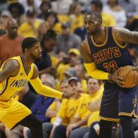 Cleveland's LeBron James (right) assesses his options as Indiana's Paul George defends on Thursday. | USA TODAY / VIA REUTERS