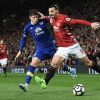 Manchester United's Zlatan Ibrahimovic (right) holds off Everton's Ross Barkley on Tuesday. | AFP-JIJI
