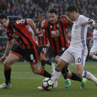 Chelsea's Eden Hazard (right) takes on the Bournemouth defense during the Blues' 3-1 win on Saturday. | AP