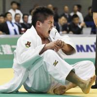 Mashu Baker screams in pain after injuring his shoulder in the first round of the men's 90-kg competition on Sunday. | KYODO