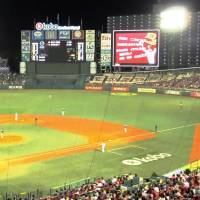 A video screen (with red ad in photo) to the right of the main scoreboard at Kobo Park Miyagi blocks the view of Rakuten Eagles games for residents of the adjacent apartment building. | WAYNE GRACZYK