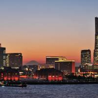 Mount Fuji serves as a backdrop in an evening view of Yokohama icons such as the Landmark Tower and Yokohama Red Brick Warehouse. | YOKOHAMA CONVENTION & VISITORS BUREAU