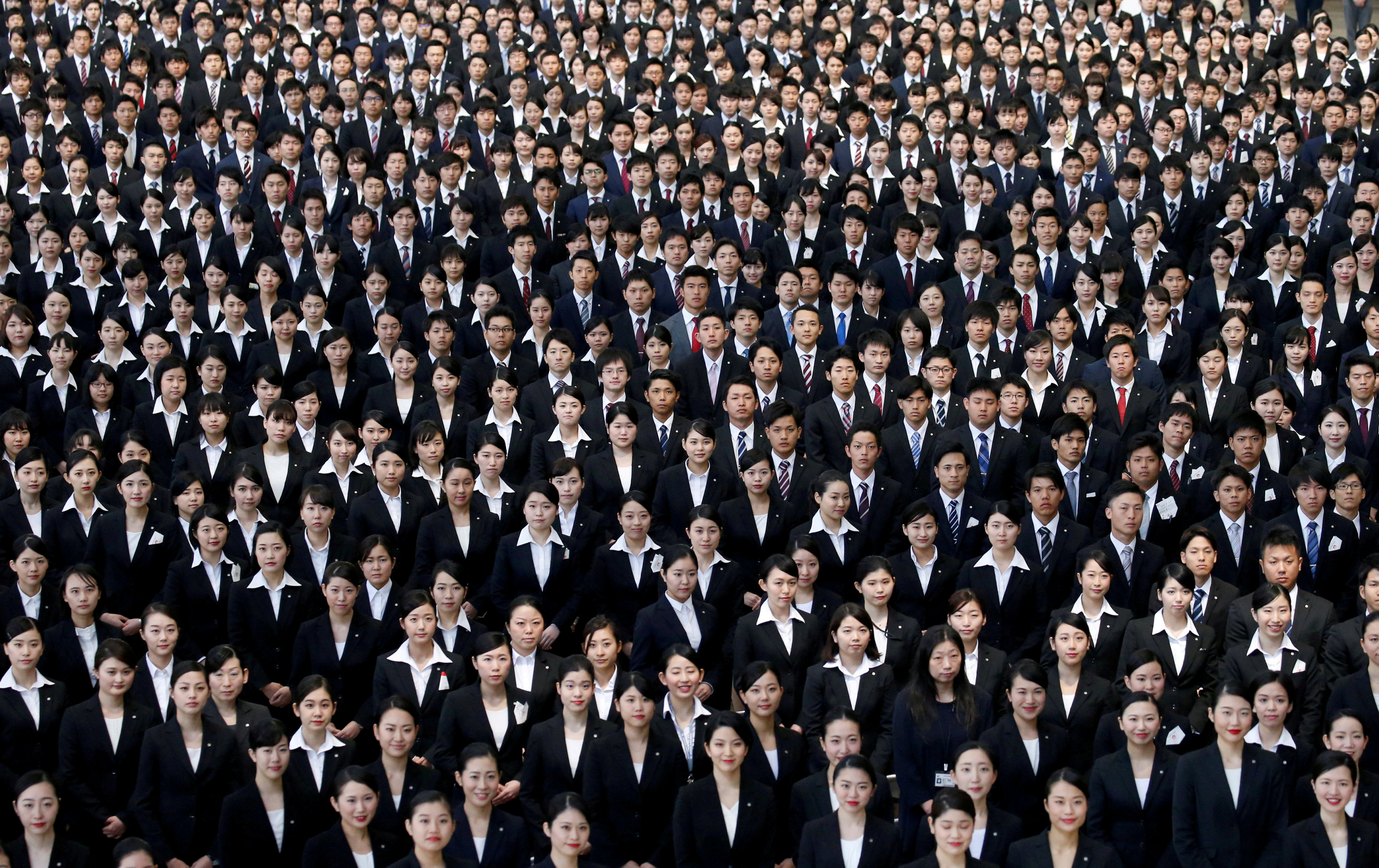 Newly-hired employees of Japan Airlines pose for photos during an initiation ceremony at a hangar of Haneda airport in Tokyo on April 3. | REUTERS