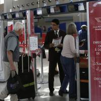 Airport staff in March inform passengers at the check-in area at Casablanca Mohammed V International Airport, Morocco, about the cabin laptop ban.   AP