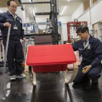 Members of a Nitori Holdings quality control team check the movement of a chair during a product test in Tokyo on April 25. In the 12 months through Feb. 20,  the firm posted its 30th consecutive year of increased profit to go along with ever-expanding sales. | BLOOMBERG