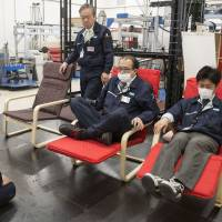 Members of a Nitori Holdings Co. quality control team try different methods of sitting on chairs during a product test in Tokyo on April 25. | BLOOMBERG