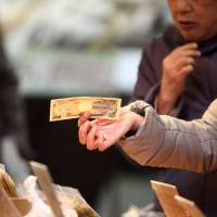 A shopper holds a bank note at a store in Tokyo's Sugamo district, a popular area among elderly people. Due to the rapidly aging population, it is predicted that the amount of money in sleeping accounts and cash left behind by people who die without heirs will increase. | BLOOMBERG