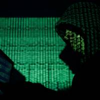 A hooded man holds a laptop computer as cybercode is projected on him in this illustration photo taken Saturday. | REUTERS
