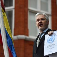 WikiLeaks founder Julian Assange, holding a report of the U.N.'s Working Group on Arbitrary Detention on his case, addresses reporters from the balcony of Ecuador's embassy in London on Feb. 5, 2016. | AFP-JIJI