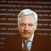 Julian Assange appears on screen via video link during a news conference London on Feb. 5, 2016. | REUTERS