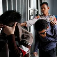 Two Indonesian men, who were later sentenced to 85 lashes of the cane for having sex together, are escorted by police into an Islamic court in Banda Aceh, Aceh province, Indonesia, Wednesday. | REUTERS
