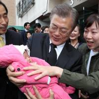 South Korean President Moon Jae-in greets his supporters and neighbors as he leaves his house in Seoul on Wednesday.   REUTERS