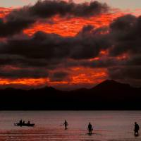 A family board their canoe at sunset in Suva, Fiji.   REUTERS