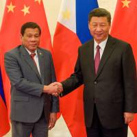 Chinese President Xi Jinping shakes hands with Philippines leader Rodrigo Duterte prior to their bilateral meeting during the 'Belt and Road' summit, at the Great Hall of the People in Beijing on Monday. | REUTERS