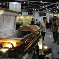 Visitors look at a paper casket at the Asia Funeral and Cemetery Expo & Conference in Hong Kong on Thursday. | AP
