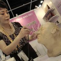 Lee Jong-lan, known as South Korea's top funerary beautician, demonstrates her airbrushing technique for covering up discolored or damaged skin on corpses at the Asia Funeral and Cemetery Expo & Conference in Hong Kong on Thursday | AP