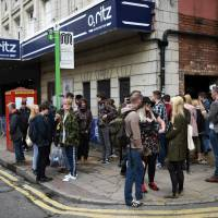 Music fans wait outside the O2 Ritz venue for a solo performance by former Oasis frontman Liam Gallagher, from which all profits will be donated to the We Love Manchester Emergency Fund, in Manchester, England, Tuesday. | AFP-JIJI