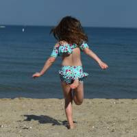 A girl runs to the water at Tod's Point Beach on the Long Island Sound in Old Greenwich, Connecticut, on Thursday. Temperatures reached into the upper 80s in the area. | AFP-JIJI