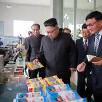 This undated picture released from North Korea's official Korean Central News Agency (KCNA) on Wednesday shows North Korean leader Kim Jong Un (center) visiting the Rangnang Disabled Soldiers' Essential Plastic Goods Factory in Pyongyang. Pentagon experts see 'shortcomings' for now in the North's quest for an ICBM capable of reaching the U.S. | KCNA VIA KNS / STR / VIA AFP-JIJI