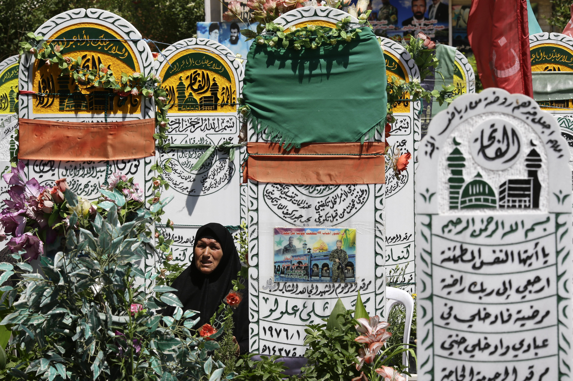 A prays at the grave of her son, who died fighting Syrian insurgents, in the Sayyidah Zaynab suburb of Damascus on Friday. Near a shrine, the new cemetery holds the remains of hundreds of Shiite fighters, testimony to the high cost of Iran's military intervention in Syria. | AP
