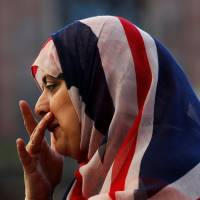 A woman wears a union jack hijab in St. Ann's Square, in central Manchester, Britain, on Friday. | REUTERS