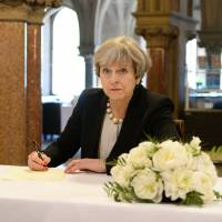 British Prime Minister Theresa May writes a message in the book of condolences for victims of Monday's attack on Manchester Arena on Tuesday at Manchester Town Hall. | REUTERS