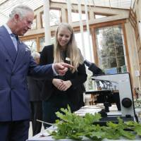 Britain's Prince Charles speaks to research assistant Nicola Kuhn about wood densities during a visit to the Royal Botanic Gardens, Kew, in London on Wednesday. | AP