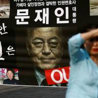 A woman walks past a placard opposing new South Korean President Moon Jae-in's policy on North Korea in Seoul on Thursday. | REUTERS