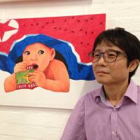 North Korean defector Song Byeok is seen with one of his pictures at an exhibition of his work in London on Tuesday. Song was a propaganda artist before defecting to South Korea where he now paints works satirizing his homeland. | EMMA BATHA / VIA THOMSON REUTERS FOUNDATION