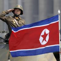 A North Korean national flag flutters as soldiers in tanks salute to leader Kim Jong Un during a military parade in Pyongyang on April 15, the 105th anniversary of the birth of the country's founder, Kim Il Sung.   AP