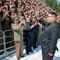 North Korean leader Kim Jong Un waves to scientists and technicians who developed the Hwasong-12 intermediate-range ballistic missile in this photo released Saturday. | KCNA / VIA REUTERS