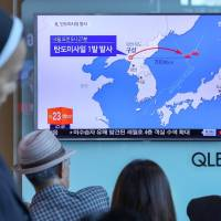 People watch a news report on North Korea firing a ballistic missile, at a railway station in Seoul on Sunday. | YONHAP / VIA REUTERS