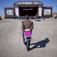 An elderly man carries a chair to as he walks toward an outdoor theater before a Jin opera performance in Yu County, in China's Hebei province, on March 31. | AFP-JIJI