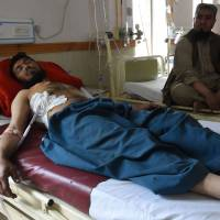 A Pakistani relative sits next to an injured victim of cross border firing, at a hospital in Quetta on Saturday. | AFP-JIJI