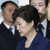 Former South Korean President Park Geun-hye arrives March 30 at the Seoul Central District Court for hearing on a prosecutors' request for her arrest for corruption in Seoul. Handcuffed, her inmate number 503 attached to her clothing, Park begins her corruption trial Tuesday in the same courtroom where a brutal dictator was sentenced to death two decades ago. | AP