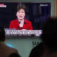 South Koreans watch a news broadcast on President Park Geun-hye at Seoul Station on Oct. 31. | BLOOMBERG