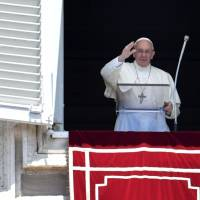 Pope Francis waves to the crowd from the window of the apostolic palace overlooking St. Peter's Square during the Regina Coeli prayer at the Vatican on Sunday. | AFP-JIJI