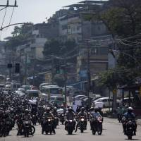 Motorcyclists who work on community transport protest during an operation in the Alemao slum complex after violent clashes between policemen and drug dealers in Rio de Janeiro Thursday. | REUTERS